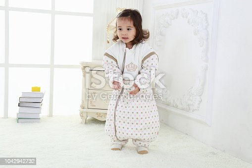 956002732 istock photo the beautife little girl in the pink bule pyjamas played in the room 1042942732