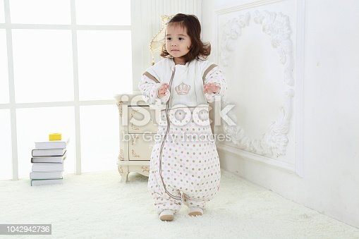 956002732 istock photo the beautife little girl in the pink bule pyjamas played in the room 1042942736