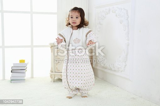 956002732 istock photo the beautife little girl in the pink bule pyjamas played in the room 1042942738