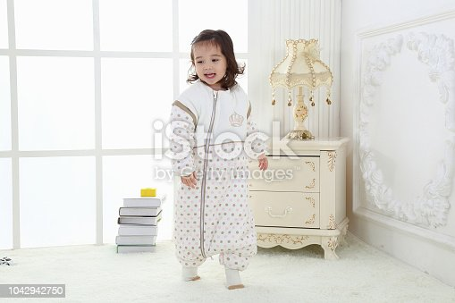 956002732 istock photo the beautife little girl in the pink bule pyjamas played in the room 1042942750