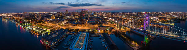 the beautiful aerial view of philadelphia downtown at night, over the benjamin franklin bridge and the piers in old city at delaware river. - philadelphia skyline stock photos and pictures