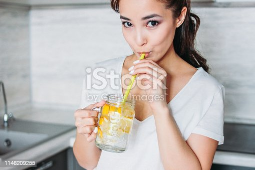 The beautiful asian girl young woman drinking glass jar with lemon water in kitchen, close up