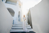 The beautiful blond hair young women bride blue in a wedding white long sexy dress on Santorini in Greece