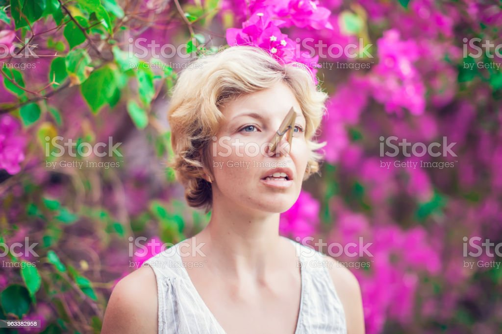The beautiful blonde with a clothespin on her nose. Runny nose....