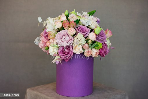 istock The beautiful bouquet of flowers in purple box on gray background 903327768