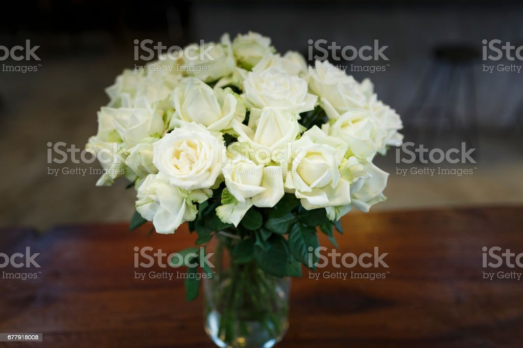 The beautiful bouquet roses in a vase on a wooden table royalty-free stock photo