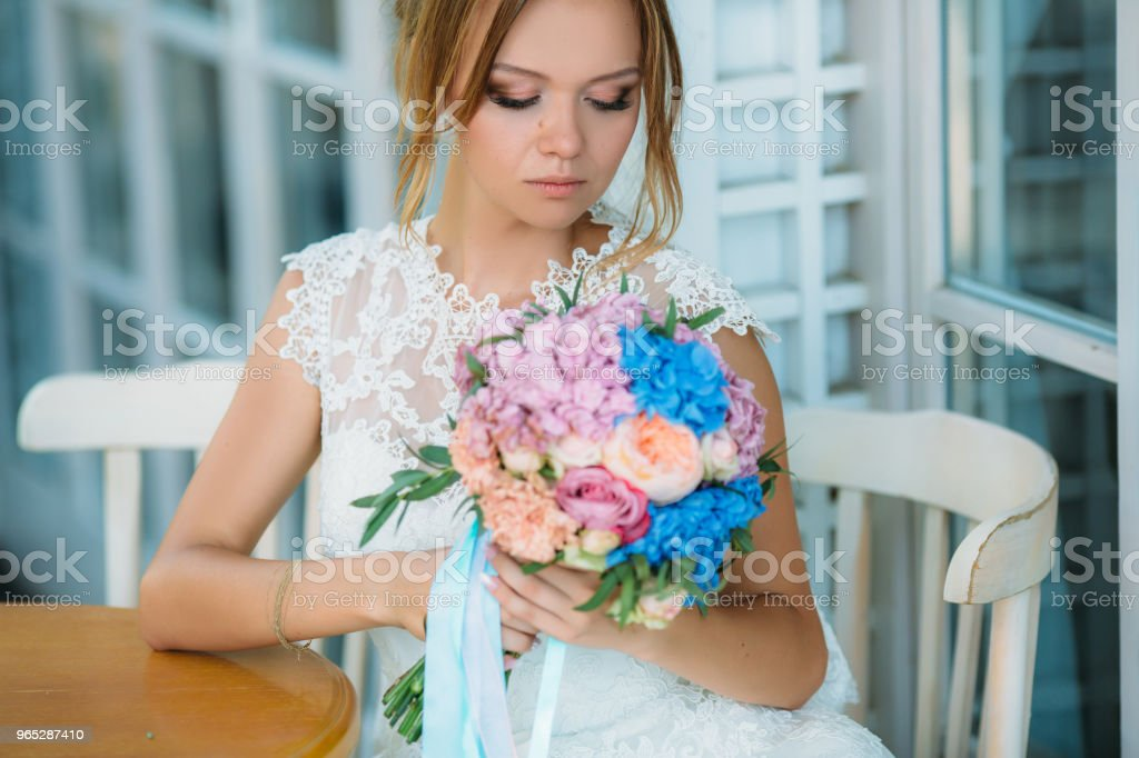 The beautiful bride lowered her eyes to her bouquet of flowers. A girl in a white dress admires the roses zbiór zdjęć royalty-free