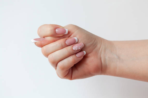 Cтоковое фото The beautiful female hand with graceful French manicure shows the sign of a fig