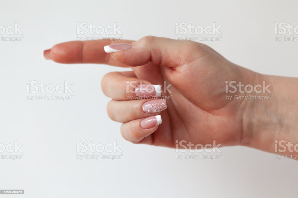 The beautiful female hand with graceful French manicure shows the sign of a direction стоковое фото