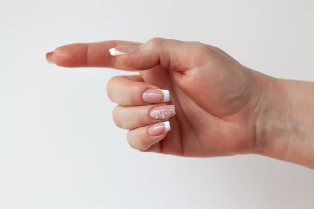 Cтоковое фото The beautiful female hand with graceful French manicure shows the sign of a direction