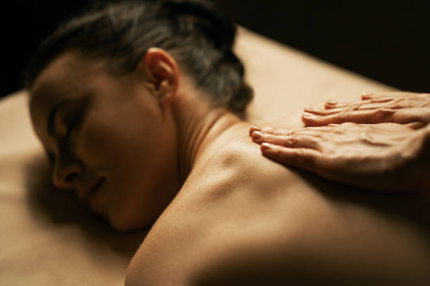 The beautiful girl has massage. Authentic image of luxury spa treatment. Warm colors, charming light. stock photo