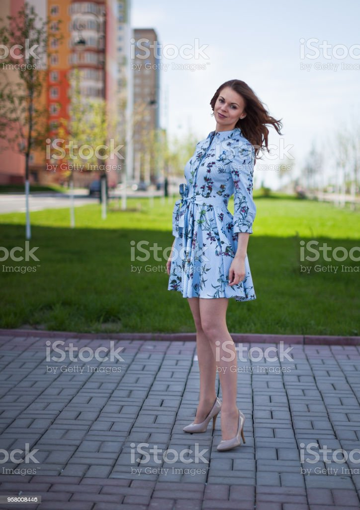The beautiful girl in a blue short dress costs against the background of the street per windy sunny day стоковое фото