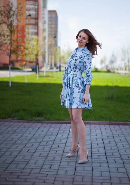 Cтоковое фото The beautiful girl in a blue short dress costs against the background of the street per windy sunny day