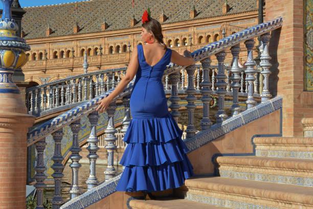 la muchacha hermosa en el vestido de flamenca azul en las escaleras - foto de stock