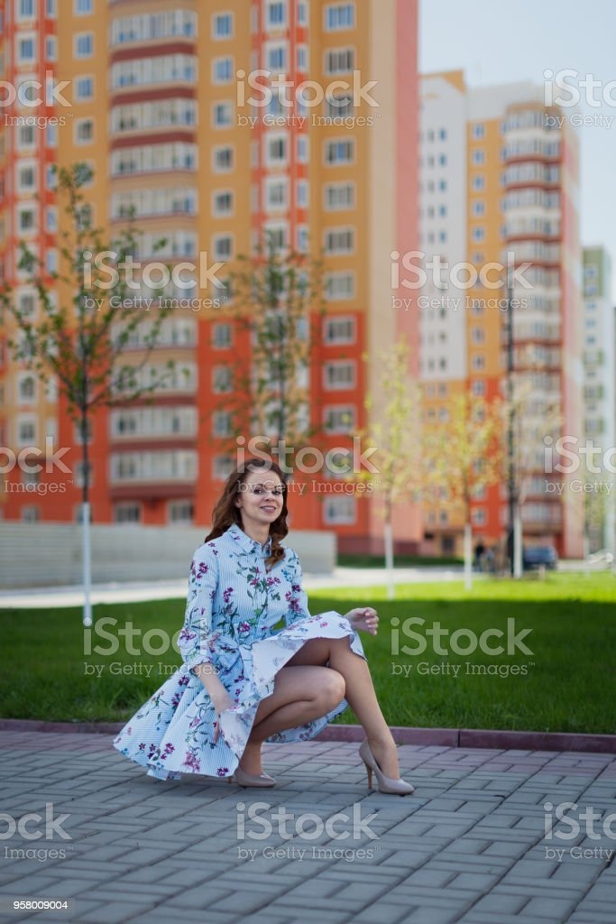The beautiful girl sits in the blue short dress lifted by wind against the background of high houses стоковое фото