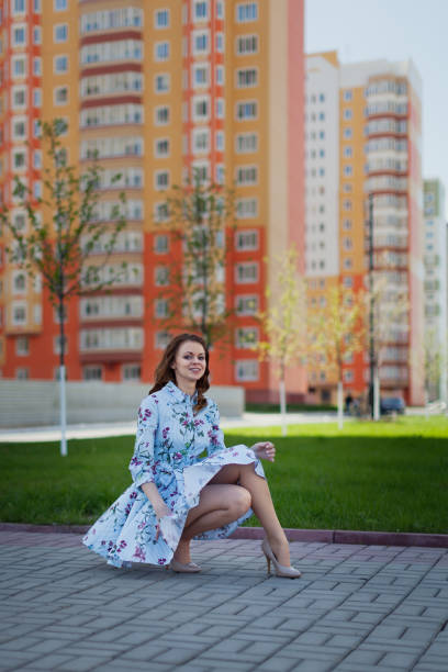 Cтоковое фото The beautiful girl sits in the blue short dress lifted by wind against the background of high houses