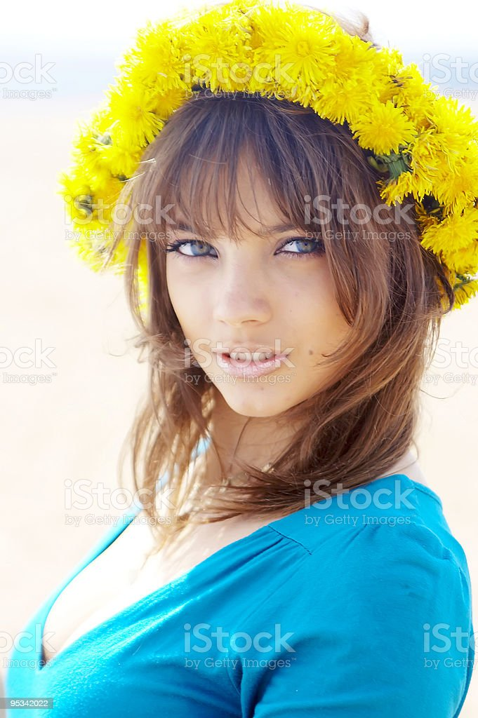 The beautiful girl with a wreath from dandelions royalty-free stock photo