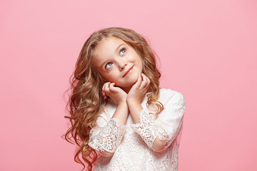 istock The beautiful little girl in dress standing and posing over white background 863697778