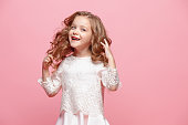 istock The beautiful little girl in dress standing and posing over white background 863706578