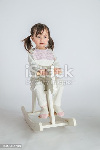 The beautiful little girl is riding a wooden horse