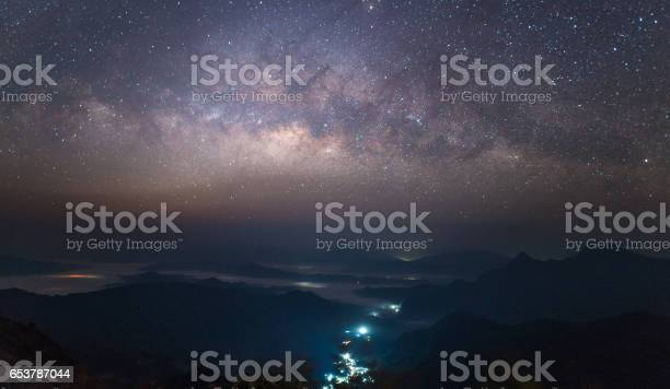 Photo of The beautiful Milky Way in the starry night over the landscape of the countryside of Thailand.