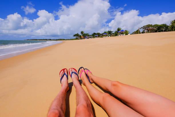 The beautiful naked legs of a couple wearing flip flops on the sandy beach Praia Do Mutari Brava, Porto Seguro, Brazil stock photo