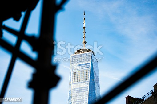 (selective focus) The beautiful One World Trade Center Tower seen through construction scaffolding in Manhattan, New York, USA.