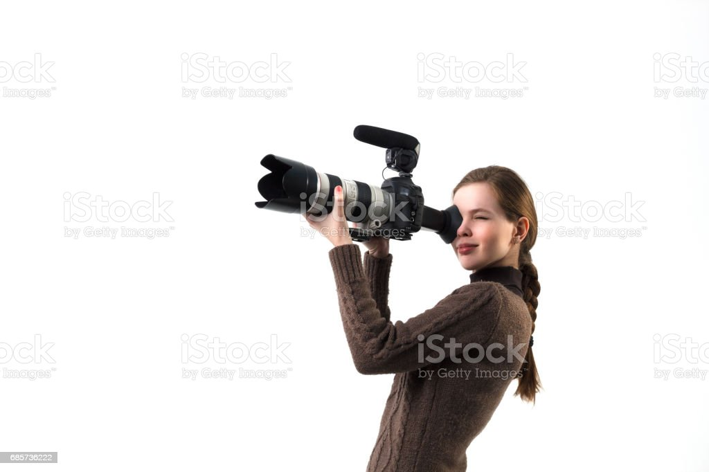 The beautiful photographer girl with professional dslr camera posing on a white background in studio. Photo learning, studying, training concept foto de stock royalty-free