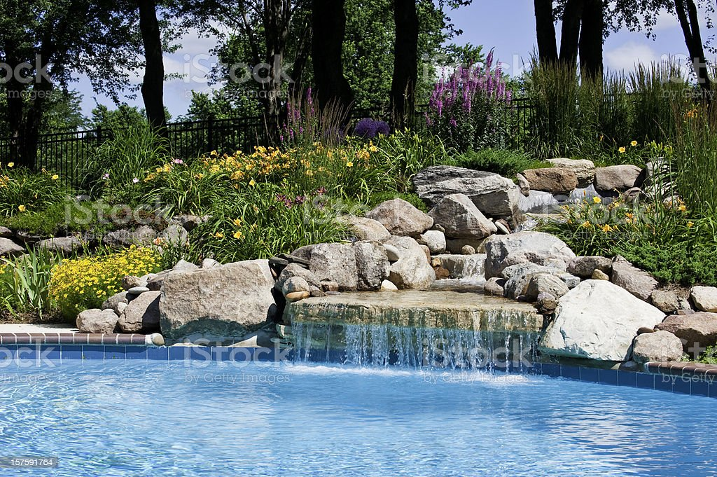 The beautiful poolside of a waterfall with rocks stock photo
