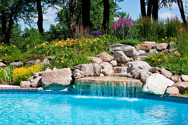 The beautiful poolside of a waterfall with rocks Beautifully landscaped backyard pool with a waterfall. backyard pool stock pictures, royalty-free photos & images