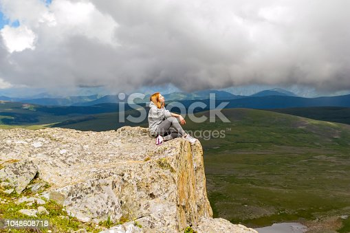 istock The beautiful red-haired girl sits and relaxing keep calm alone on the edge of a cliff in the rays of light on a rock Altai mountains on a background of blue sky with big gray clouds and landscape 1048608718
