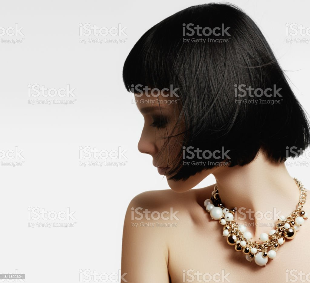 The beautiful woman in expensive pendant close-up. Beautiful young woman model with perfect makeup wearing jewelry. Fashion portrait of beautiful luxury woman with jewelry stock photo