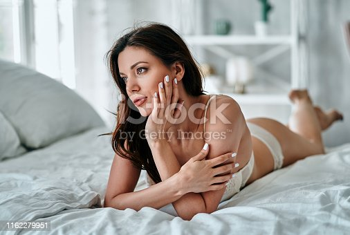 The beautiful woman in underwear laying on the bed