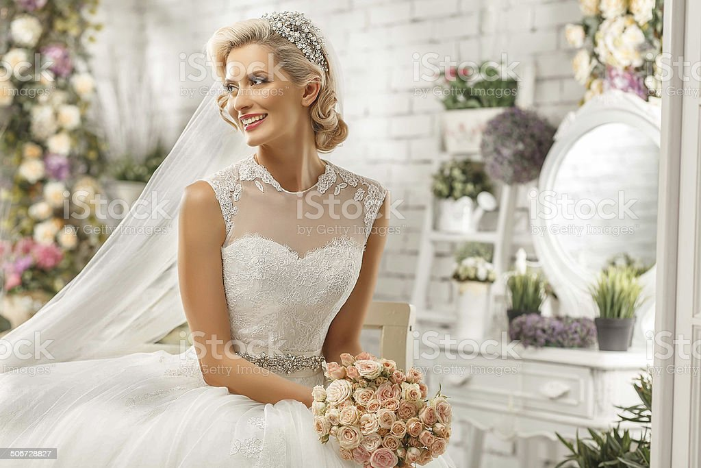 The beautiful  woman posing in a wedding dress stock photo