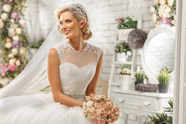 The beautiful  woman posing in a wedding dress stock photo