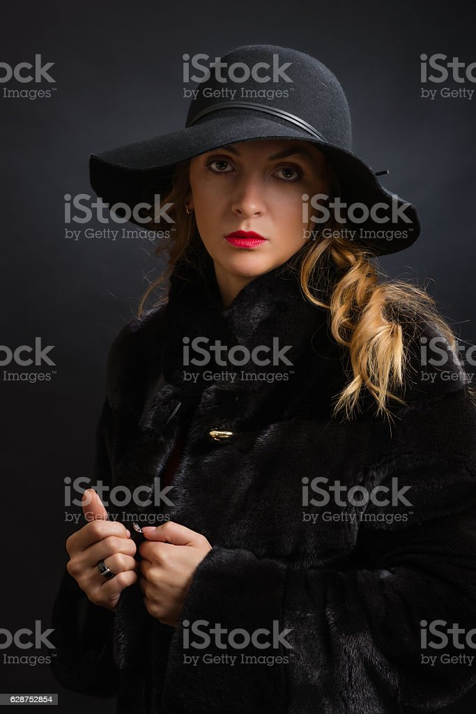 The beautiful young girl in a black hat with wide стоковое фото