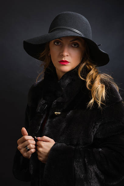 Cтоковое фото The beautiful young girl in a black hat with wide