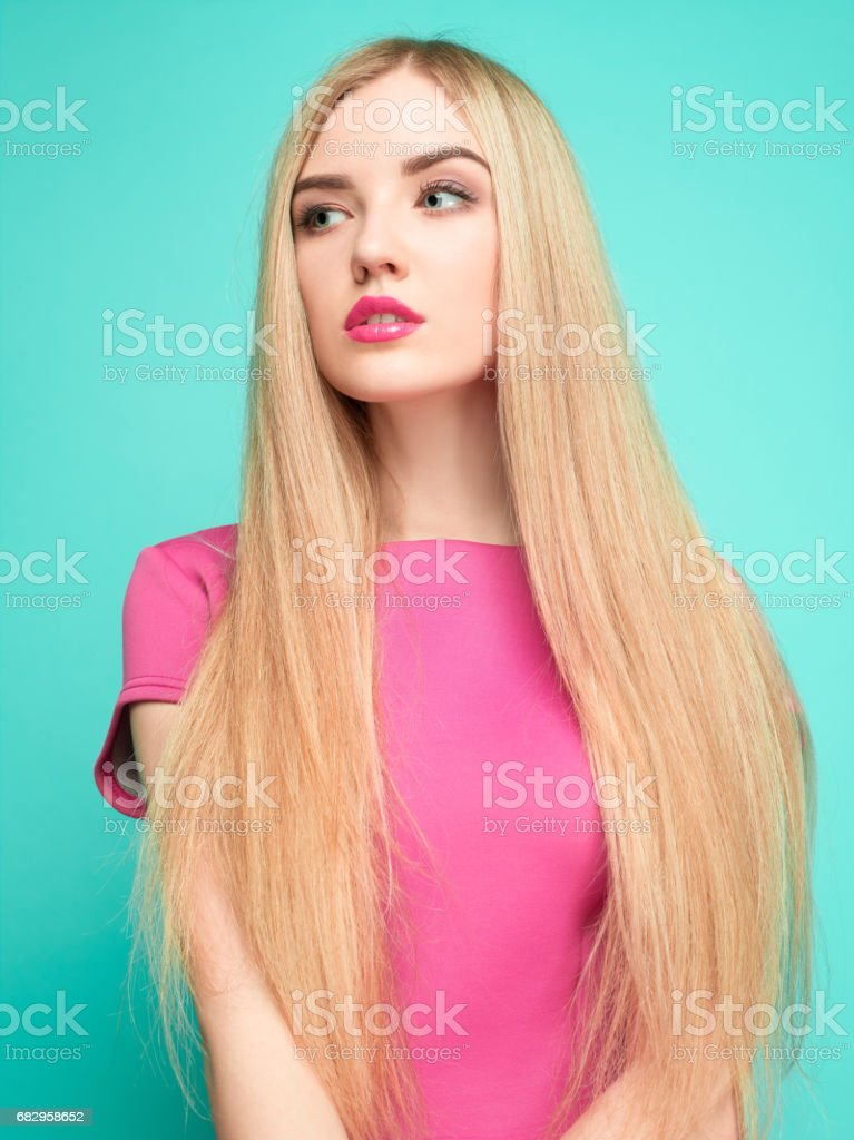 The beautiful young woman in pink mini dress posing at studio foto de stock royalty-free