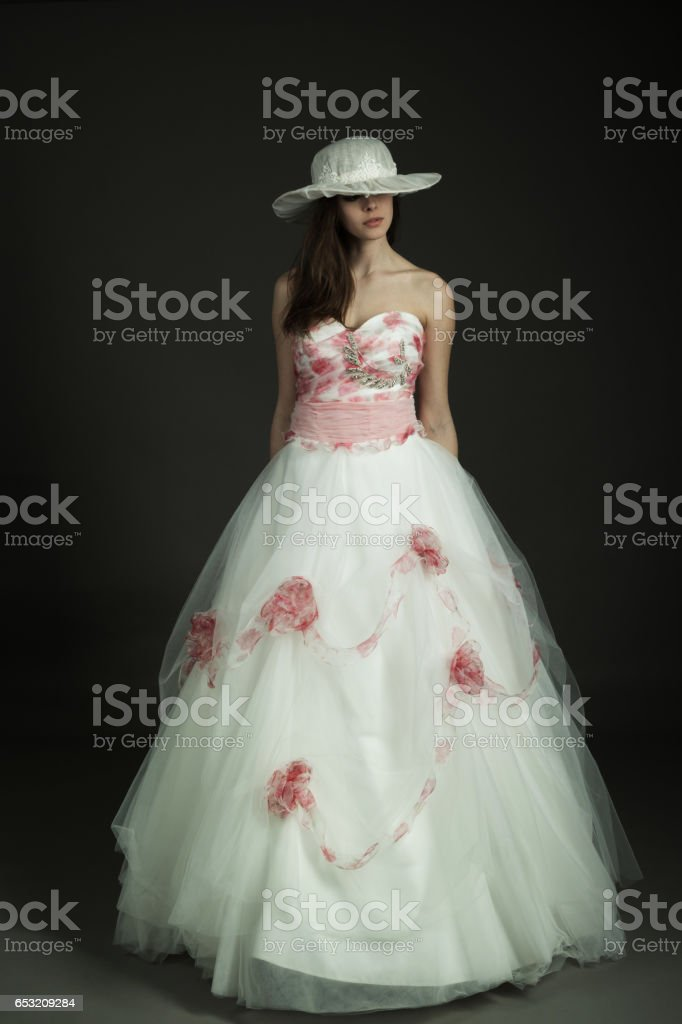 The Beautiful Young Woman Posing In A Wedding Dress Over