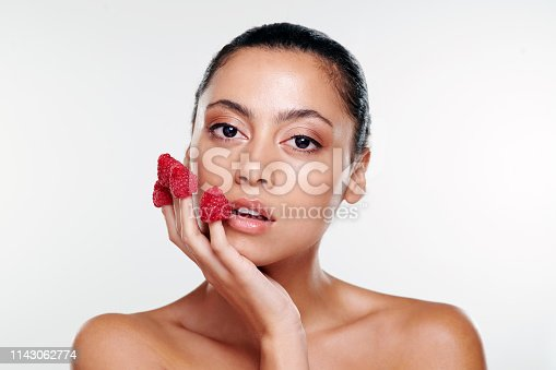 Shot of a beautiful young woman with raspberries on her fingers against a studio background