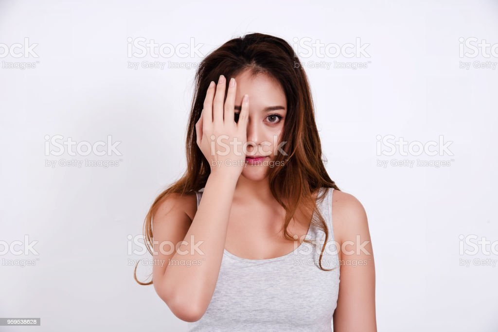 The beauty lady with long hair is raise her right hand to close her right eye,left eye is looking straight with little smile, stock photo