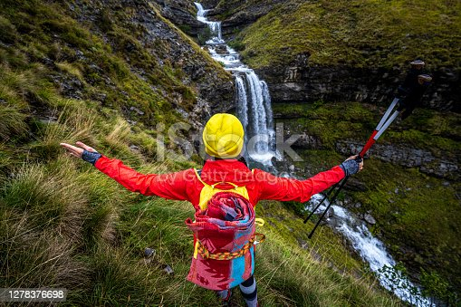 Woman adventurer mesmerised by the beauty of a waterfall and the whole mountain surrounding where she is hiking.