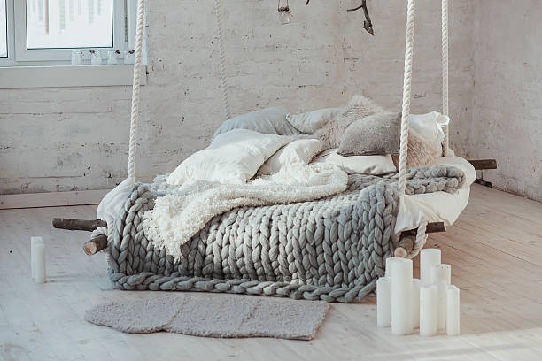 The bed suspended from the ceiling. Grey big cozy blanket stock photo