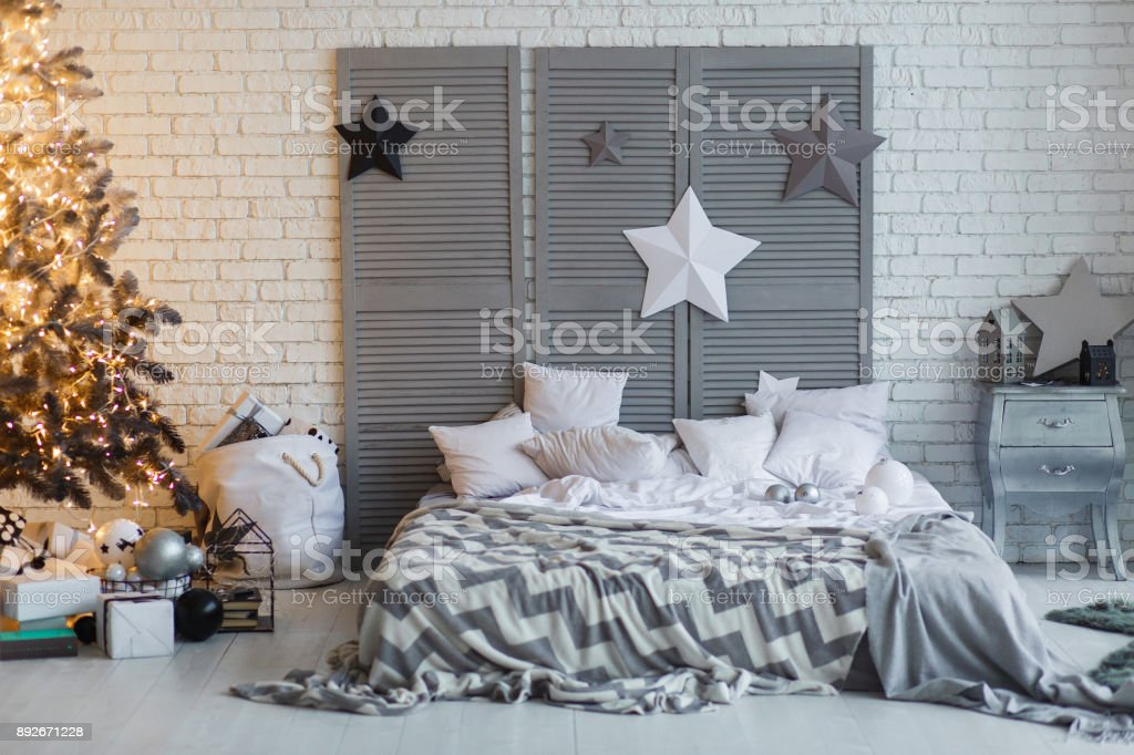 The bedroom decorated for Christmas. Cozy gray home interior. New year decoration. bright bedroom room with large double bed. Christmas tree with shyning garland. stock photo