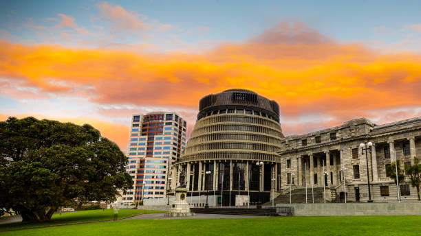 The Beehive, Wellington, New Zealand New Zealand parliament building the beehive under a vibrant orange sunset. wellington new zealand stock pictures, royalty-free photos & images