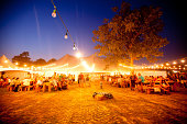 Manchester, United States - June 10, 2011: Strings of lights illuminate the alluring Beer Garden tent at Bonnaroo music and arts festival as festival goer crowd around picnic tables or seat themselves on hay bales to relax and enjoy a craft micro brew.