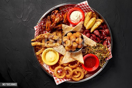 istock The beer plate with spicy chicken wings, calamari rings, fries onion rings, cheese balls, breaded, tartar sauce and garlic 907853660