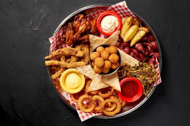 配有辣雞翅、魷魚環、炸洋蔥圈、芝士球、麵包屑、韃靼汁和大蒜的啤酒盤 - 開胃菜 個照片及圖片檔