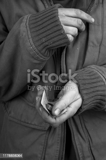 the beggar in a jacket froze and asks for cash help,concept: loneliness and poverty.