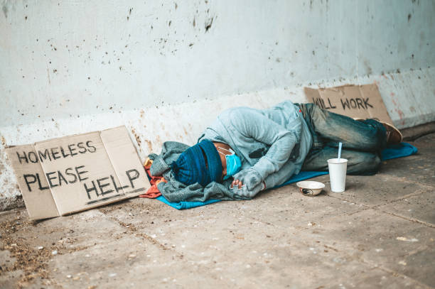 The beggars lay on their side of the street with dirty clothes. stock photo